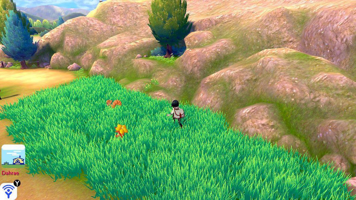 Un entrenador Pokémon se acerca sigilosamente a un Vulpix