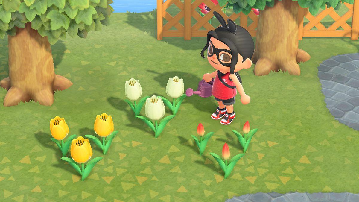 Un personaje de Animal Crossing se encuentra cerca de una serie de tulipanes.
